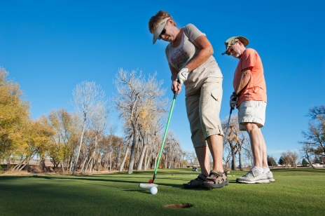 Joan Renelt tries to put a golf ball into the hole as her husband Tim looks on at the Rapid City Executive Golf Course on an unusually warm November afternoon.