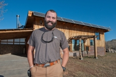"Jared ""Cappie"" Capp stands in front of his energy-independent house on Friday morning in Spearfish. Capp has created a house that generates its own electricity, and uses various building methods and materials to make the house entirely self sustaining."