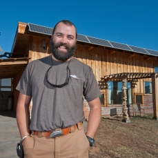 """Jared """"Cappie"""" Capp stands in front of his energy-independent house on Friday morning in Spearfish. Capp has created a house that generates its own electricity, and uses various building methods and materials to make the house entirely self sustaining."""