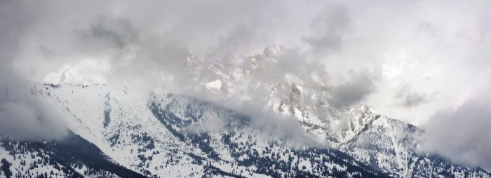 The Grand Teton is partially shrouded by passing fog. Grand Teton National Park.