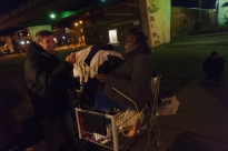 Paul, right, laughs as Gary pretends to tie him to his cart outside of the Charleston Men's Emergency Shelter in Charleston, W.Va., on Wednesday night, December 13, 2017.