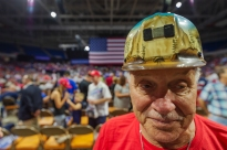 John Berta of Oceana in Wyoming County, W.Va, shows off his mining helmet before President Trump takes the stage at a rally in support of the Senate candidacy of Attorney General Patrick Morrisey, Monday, Aug. 21, 2018, at the Charleston Civic Center in Charleston, W.Va. Berta worked as a coal miner for 36 years.