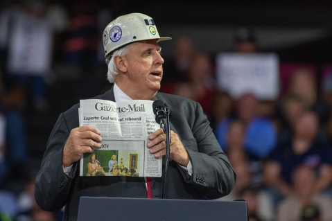 West Virginia Governor Jim Justice criticizes an article by the Charleston Gazette-Mail while holding a copy of the newspaper during a rally by President Trump in support of the Senate candidacy of Attorney General Patrick Morrisey, Monday, Aug. 21, 2018, at the Charleston Civic Center in Charleston, W.Va.
