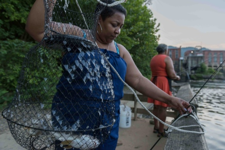 CRAIG HUDSON | Gazette-Mail Anjeanette Spencer of Columbus OH hoists up her fish as her aunt Catherine Saunders continues to cast her line at Kanawha Falls outside of Glen Ferris, W.V., on Wednesday, July 19, 2017.