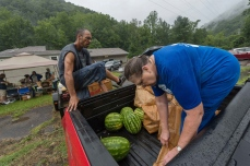 CRAIG HUDSON | Gazette-Mail Nada White and Joseph Miller sort through orders at a farmer's market outside of the Cabin Creek Health Center in Dawes , W.V., on Thursday, July 27, 2017.