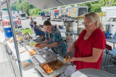 CRAIG HUDSON | Gazette-Mail Carol Bellamy, right, and Cickie Cox make chili dogs before the nigh't festivities in Iaeger, W.V., on Tuesday, August 01, 2017.