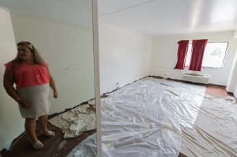 CRAIG HUDSON | Gazette-Mail Belinda Harnass, Housing Authority director for Mingo County, looks into a room at the Sycamore Inn in Williamson, W.V., on Wednesday, August 09, 2017.