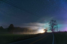 Lights from a house are illuminated in fog that blankets the road ahead under a starry sky in rural West Virginia