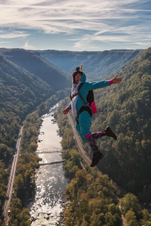 """Johnny """"Tarzan"""" Copley of Salt Lake City base jumps while dressed as a unicorn during the 40th annual Bridge Day on the New River Gorge bridge in Fayetteville, W.V., on Saturday, October 21, 2017."""