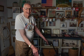 Dyer Stanard, who participated in the invasion of Normandy and other strategic campaigns of World War II, poses alongside his medals, pictures, patches and other memorabilia inside his garage in Hurricane, W.V., on Wednesday, July 11, 2018.